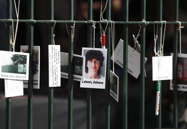 Detalle de fotografías en una reja dejadas el 19 de marzo de 2015, durante un homenaje a las víctimas del atentado contra la embajada de Israel en Buenos Aires, Argentina. (Archivo/EFE)