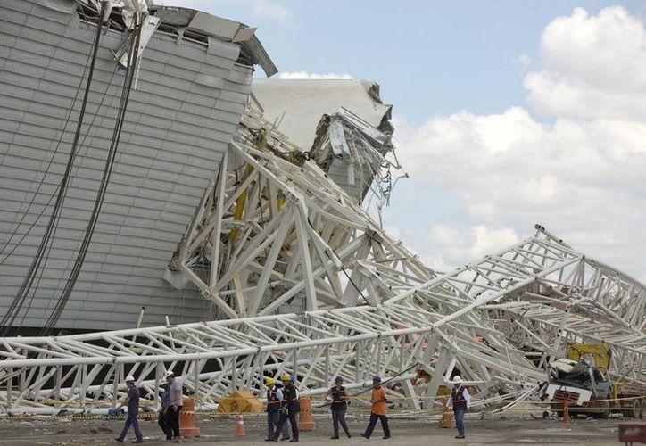Ingenieros y técnicos inspecciona el lugar del desastre en el estadio de Sao Paulo para tratar de determinar cuándo podría reanudarse la construcción. (Agencias)