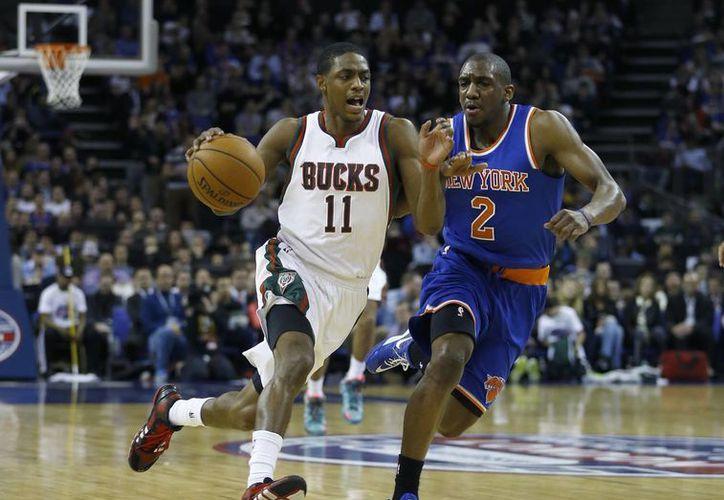 Brandon Knight (i), de Bucks, trata de pelearle el balón a Langston Galloway, de Knicks, en partido de la NBA jugado en Londres. (Foto: AP)