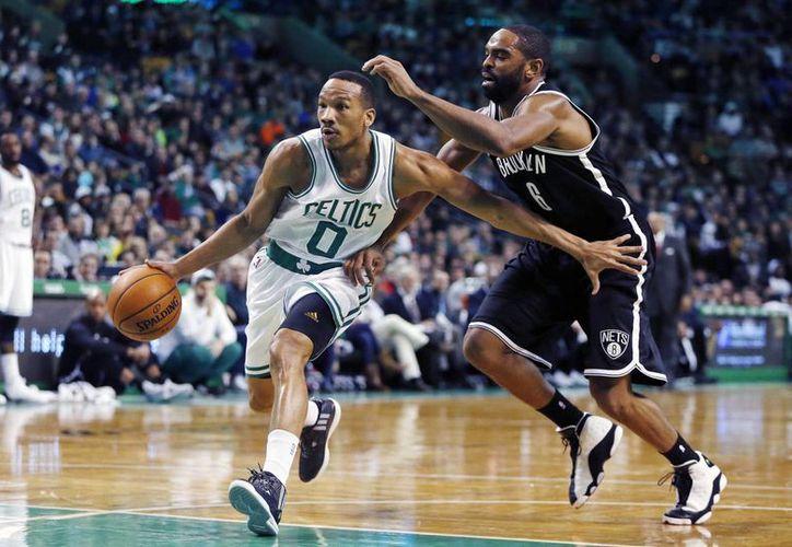 Avery Bradley (0), de Celtics, se adelanta a Alan Anderson (6), de Nets, en el segundo cuarto del partido de NBA ganado por el quinteto de Brooklyn. (Foto:AP)