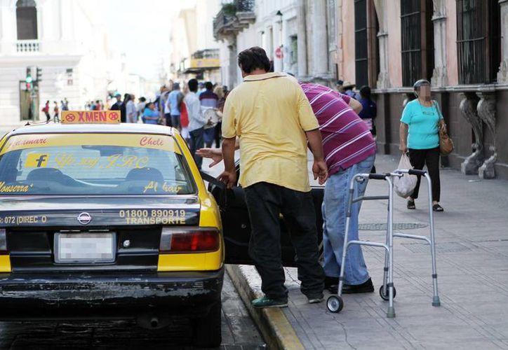 Muchas organizaciones abren las puertas a los discapacitados y toman en cuenta su capacidad y no su discapacidad. Imagen de una persona con una andadera al subir a un taxi en el centro de la ciudad. (Milenio Novedades)