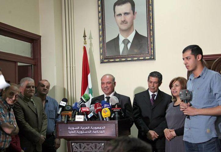 El portavoz de la Corte Suprema Constitucional siria Majid Khadra (c) anuncia la lista definitiva de candidatos presidenciales en Damasco, Siria. (EFE)