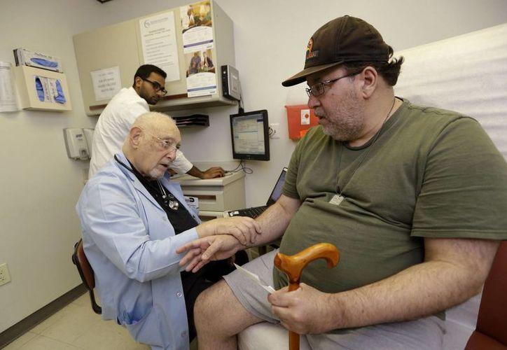 el Dr. Arnold Oper conversa con el paciente José Cabrera, que no tiene seguro médico, en el Centro de Salud Doris Isen en Cutler Bay, Florida. (Agencias)