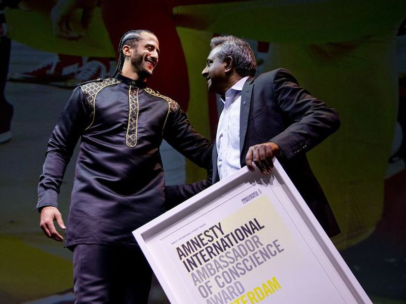 Former NFL quarterback and social justice activist Colin Kaepernick, left, receives the Amnesty International Ambassador of Conscience Award for 2018 from Amnesty International Secretary General Salil Shetty in Amsterdam.