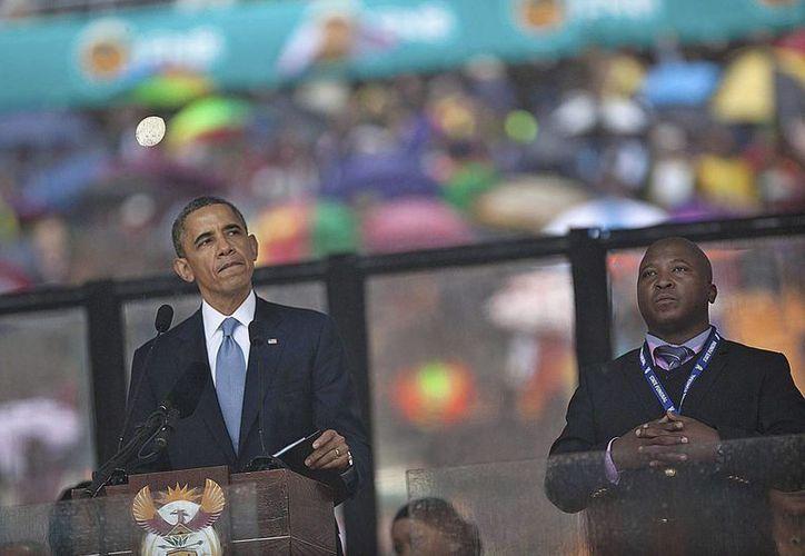 Thamsanqa Jantjie (der.) durante la intervención del presidente de EU, Barack Obama, en la ceremonia en memoria del fallecido expresidente sudafricano Nelson Mandela en el estadio FNB de Johannesburgo, Sudáfrica. (EFE/Archivo)