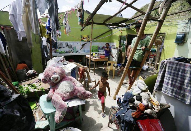 Una familia permanece en una casa afectada por fuertes vientos y lluvias tras el paso del tifón Rammasun en Gumaca, Filipinas. (EFE)
