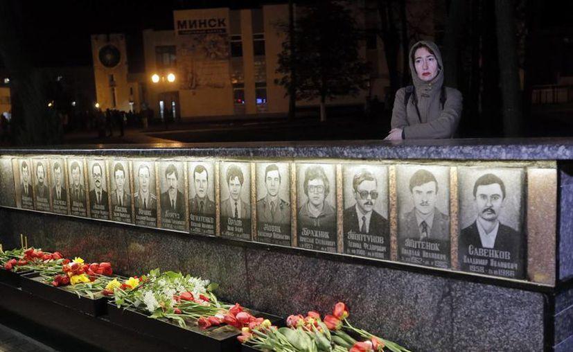 Una familiar de una víctima de Chernóbil coloca flores en las fotos cerca del monumento levantado para conmemorar a las víctimas de la explosión de Chernóbil en Kiev, la capital de Ucrania. (Foto AP/Efrem Lukatsky)