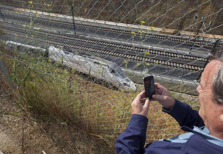 Los restos del tren aún permanecen a un costado de las vías. (Agencias)