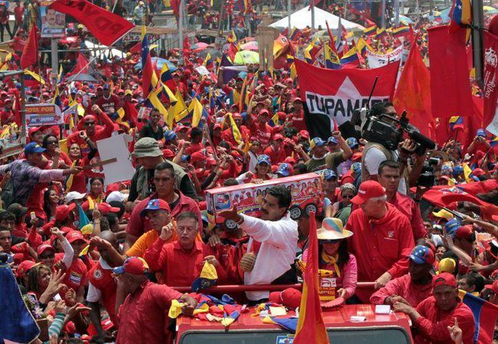 Nicolás Maduro saluda a la multitud, mientras sostiene un autobús de juguete. (Agencias)