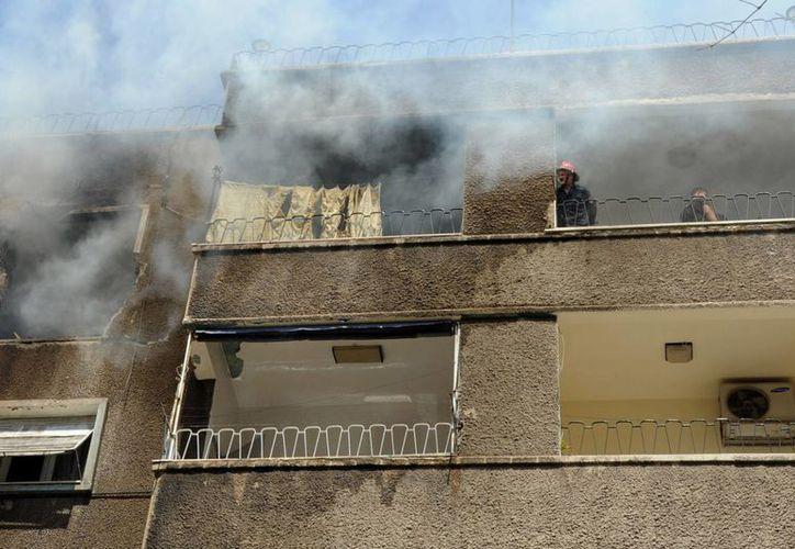 Bomberos tratan de extinguir un incendio después de que un misil se impactó contra un edificio en Damasco. (Agencias)