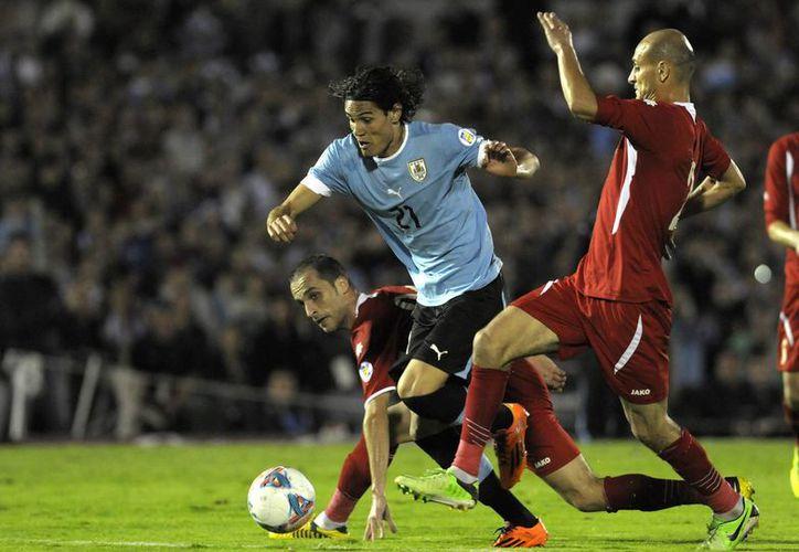 Hatem Aqel (atrás), Edinson Cavani (c) y Moahmmad Alomeiri pelean por el balón en el ríspido partido de vuelta en Montevideo. (Agencias)