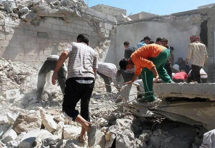 Sirios inspeccionan escombros de unas casas destruidas tras un ataque aéreo del gobierno sirio en Alepo, Siria. (Agencias)