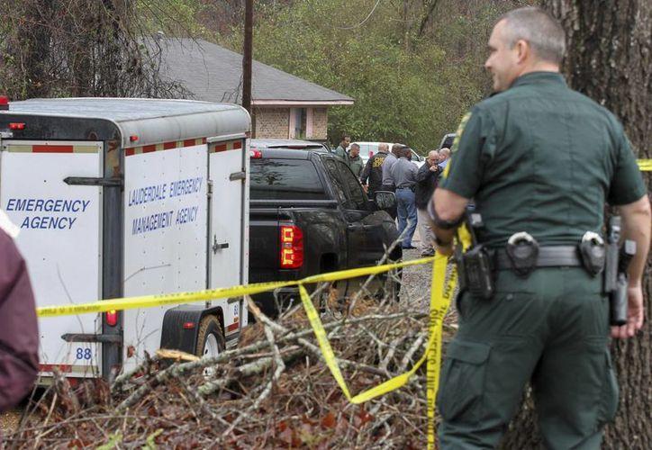 Imagen de las autoridades, del condado de Lauderdale, mientras investigan la muerte por disparos de cuatro miembros de una familia en Toomsuba, Misisipi. (Paula Merritt / The Meridian Star vía AP)