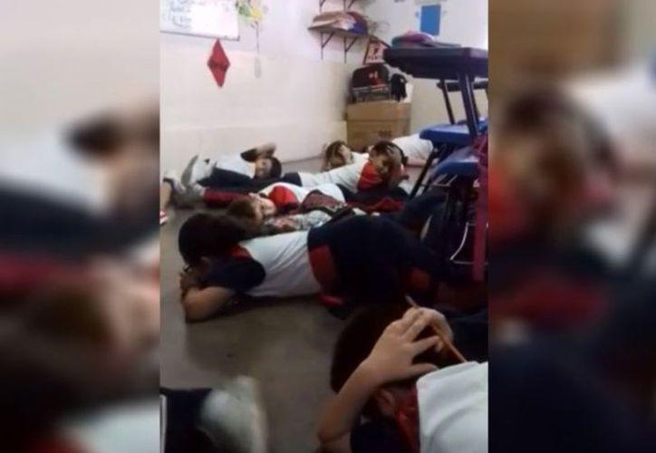 La docente comenzó a cantar junto con los pequeños durante un tiroteo. (Captura YouTube)