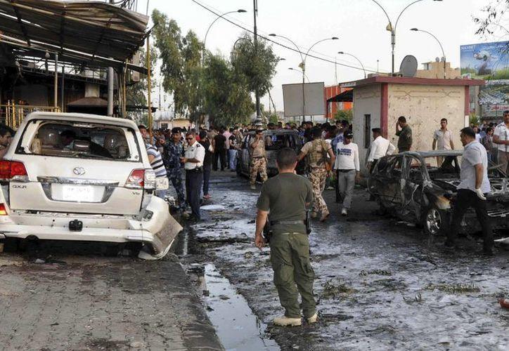 Fuerzas de seguridad y varios civiles observan en las afueras de un mercado donde se registró un ataque con coche bomba en Maiduguri. (EFE)