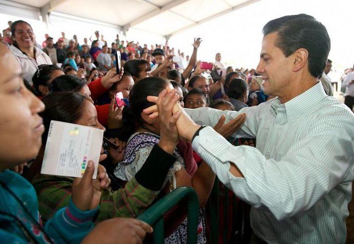 Peña Nieto saluda a la gente durante la inauguración de obras de electrificación y entrega de apoyos, entre ellos de Liconsa, en Michoacán. (presidencia.gob.mx)