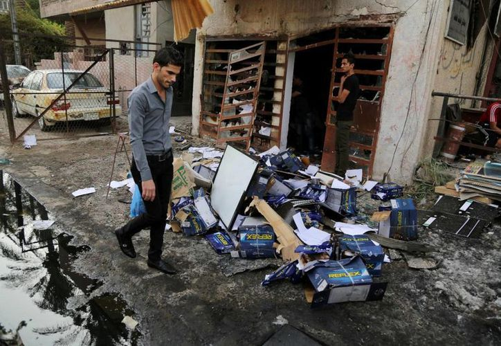 Imagen del 10 de junio de 2015 en el que se ve a civiles inspeccionando el lugar de un atentado con coche bomba en una calle de Bagdad, Irak, país que vive cotidianamente ataques terroristas . (Agencias)