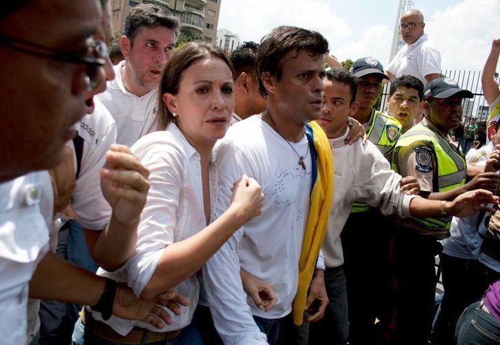 Leopoldo López (cubierto con la bandera venezolana) enfrentará un proceso por los delitos de homicidio intencional, terrorismo y lesiones graves, entre otros. (Agencias)