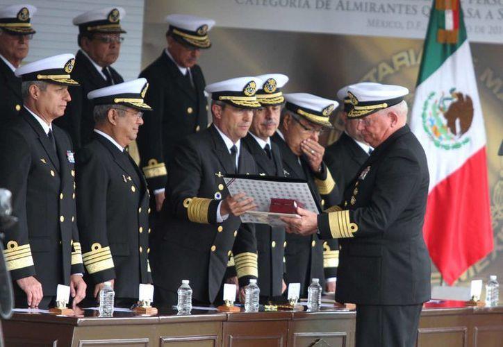 Uno de los almirantes que pasó a retiro recibe un reconocimiento de parte del titular de la Semar. (Notimex)