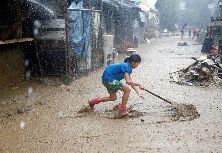 Una niña intenta desasolvar el lodo acumulado por las lluvias en Filipinas. (EFE)