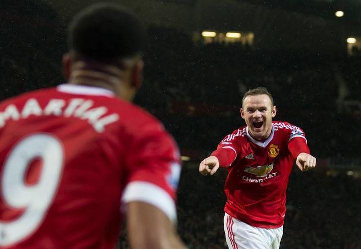 Rooney (de frente) y Martial anotaron los goles que le dieron el triunfo al Manchester United sobre el Swansea City, en la Premier League, lo que significó un respiro para el DT de los Red Devils, Louis   van Gaal. (AP)