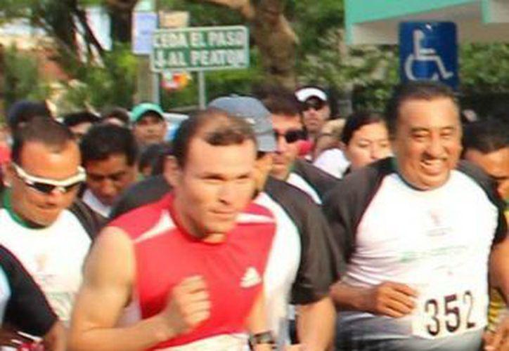 Enrique Cerón Viana (de rojo) se impuso en la categoría varonil de la carrera de la Segey. (Milenio Novedades)