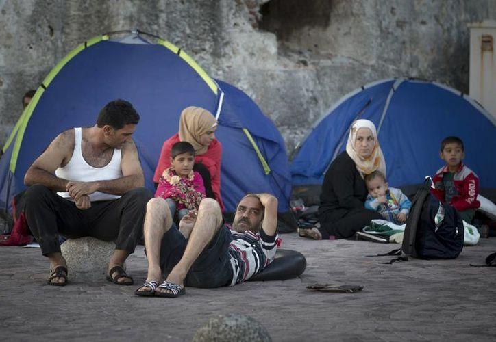 Inmigrantes descansando junto a sus tiendas mientras esperan a ser registrados en la isla sureña de Kos, en Grecia. (Agencias)