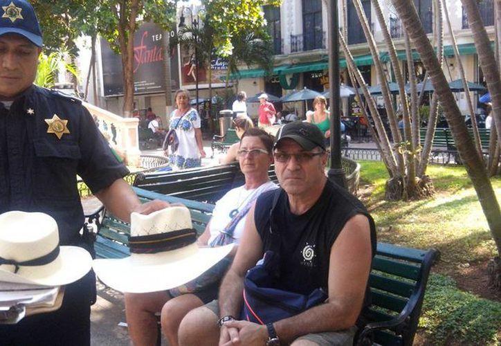 Imagen de los turistas June Hazen Elaine y Anthony Traficante después de negociar con la devolución de su dinero por unos sobreros sobre valuados. (Milenio Novedades)