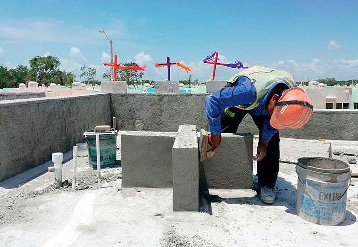 Para aminorar los candentes rayos del sol, los trabajadores de la construcción utilizan camisas de manga larga; portan chalecos y cascos porque así lo marca el reglamento de trabajo. (Foto: Redacción / SIPSE)