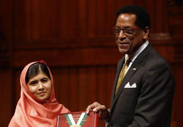 El director de la Fundación Harvard y profesor de Neurología en la Escuela Médica de Harvard Dr. S. Allen Contador, entrega el premio Peter J. Gomes Premio Humanitario a Malala Yousafzai. (Agencias)