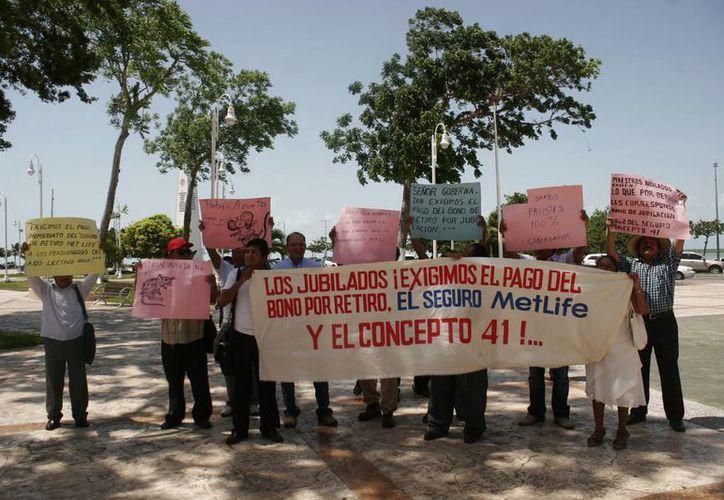 Un grupo de 20 maestros manifestándose en los bajos del Palacio de Gobierno. (Harold Alcocer/SIPSE)