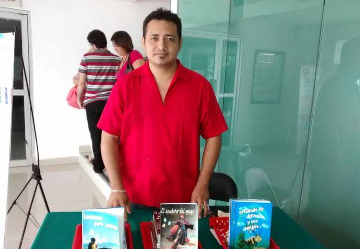 Javier Be busca mostrar a las personas una mejor perspectiva de vida, a través de sus historias fantásticas y vivenciales. En la foto, el escritor yucateco posa junto a sus tres obras literarias. (Milenio Novedades)