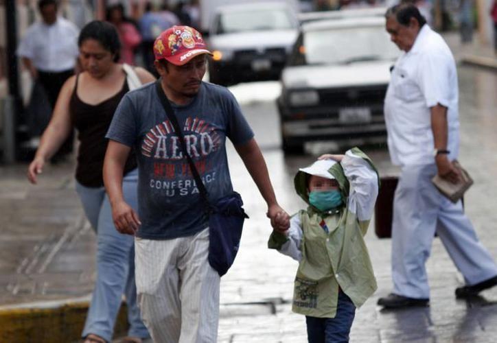 Especialistas recomiendan cuidar más a los niños para evitar enfermedades respiratorias. Imagen de contexto de un padre de familia y su hija en el centro de Mérida. (Milenio Novedades)