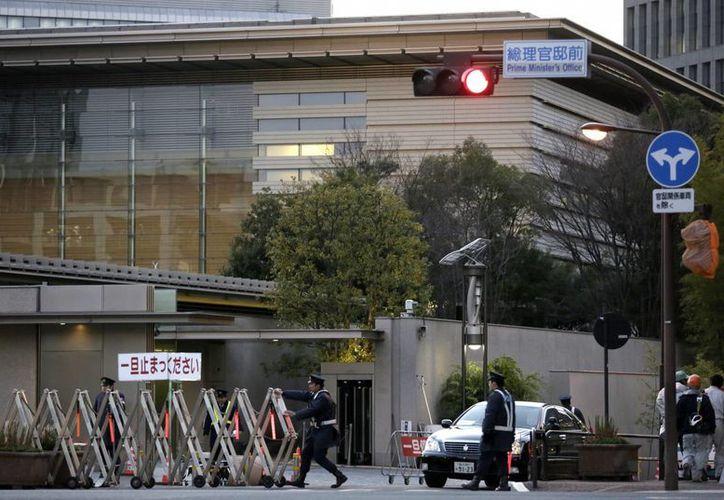 Un policía abre la reja de seguridad de la residencia oficial del Primer Ministro para permitir la salida de un vehículo del recinto en Tokio, Japón. (EFE/Archivo)