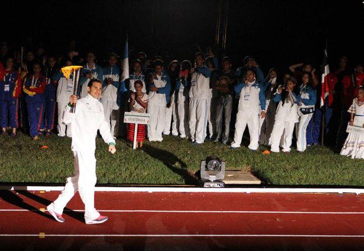 El clavadista Rommel Pacheco, portando la antorcha de los Jedecac 2015 durante la inauguración en el estadio 'Salvador Alvarado'. (César González/SIPSE)