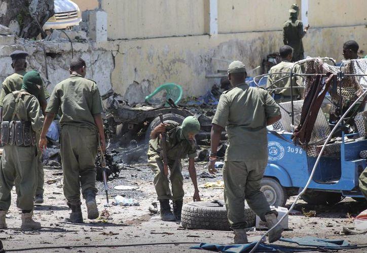 Miembros de las Fuerzas de Seguridad somalíes congregados delante de un edificio gubernamental atacado por yihadistas en Mogdiscio, Somalia hoy. (EFE)