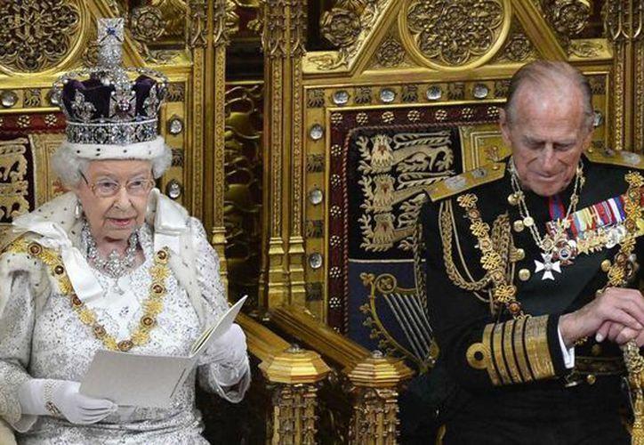 Mientras la reina Isabel II (i) daba a luz al príncipe Carlos, el príncipe Felipe, duque de Edimburgo (d), estaba ocupado jugando squash. (zoomnews.es)