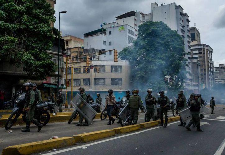 Miembros de la Guardia Nacional Bolivariana (GNB) disparan gases lacrimógenos durante una protesta en el centro de la ciudad. (EFE)