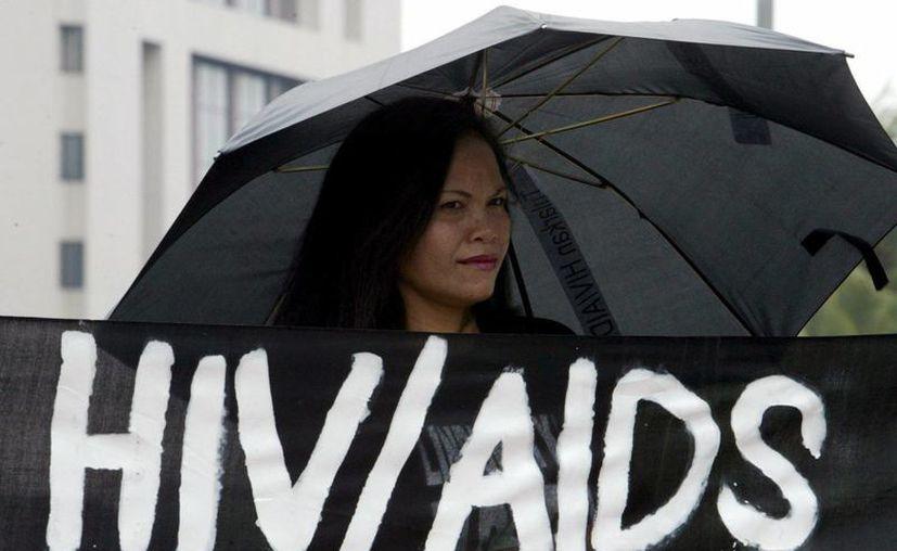 Una activista indonesia con paraguas durante una protesta contra la discriminación de las personas seropositivas en Yakarta, Indonesia. (Archivo/EFE)