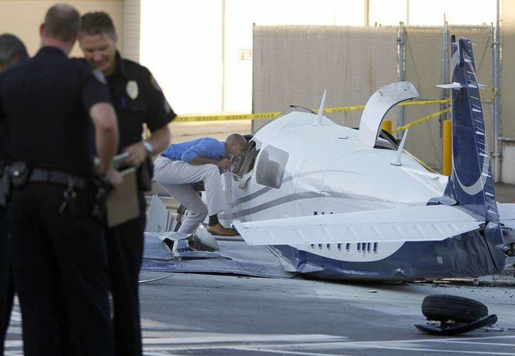 Agentes se observan cerca de donde cayó el miércoles el monomotor Mooney M-20L en un estacionamiento entre los comercios Costco y Target. (Foto: AP)