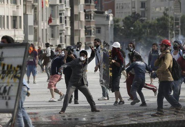 Manifestantes turcos lanzan piedras contra la policía durante los disturbios en la plaza Taksim. (EFE)