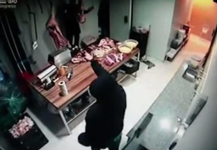 El asaltante tuvo que desenganchar por sí mismo la carne que se llevó pues el dependiente del lugar no supo cómo reaccionar. (Captura de pantalla/YouTube)