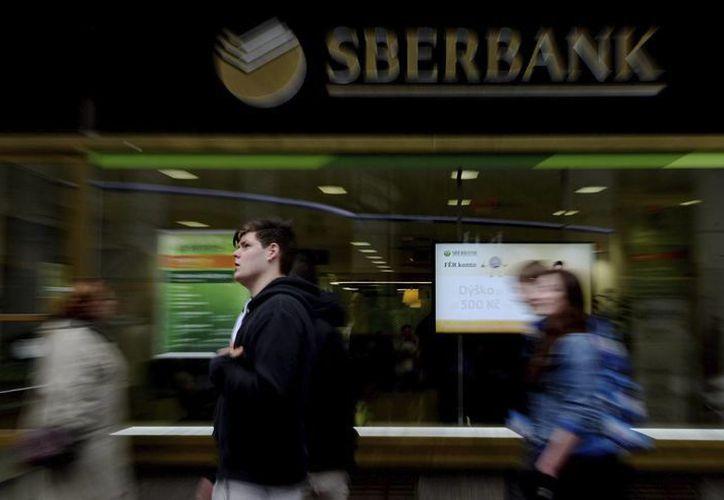 Varias personas pasan al lado de una sucursal del mayor banco de Rusia, Sberbank; quien fue sancionado por el Departamento del Tesoro de E.U. (EFE/Archivo)