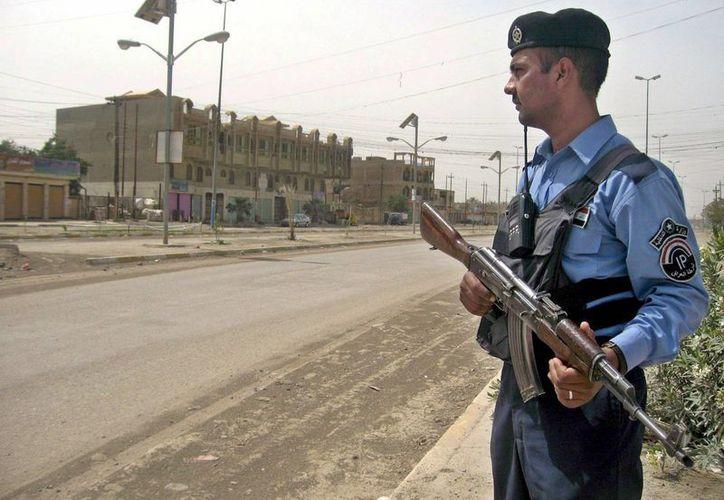 Imagen de un policía iraquí haciendo guardia en una calle desierta de Bagdad, después del toque de queda que estaba impuesto en esta ciudad. (Archivo/EFE)