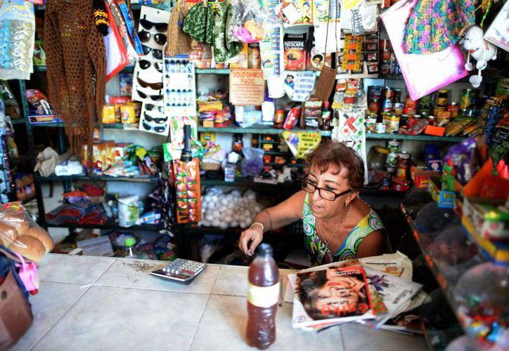 Los festejos decembrinos generaron un repunte en sus ingresos. Imagen de una mujer mientras atiende una tiendita en Mérida. (Milenio Novedades)
