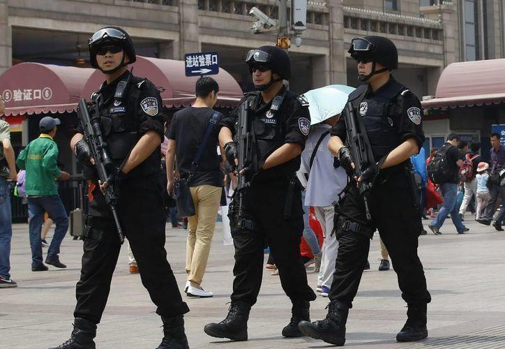 Policías vigilan los alrededores de la estación de tren de Pekín, un día después de que el pasado 22 de mayo de 2014, un atentado causara 31 muertos y 94 heridos en la región china de Xinjiang. (EFE)