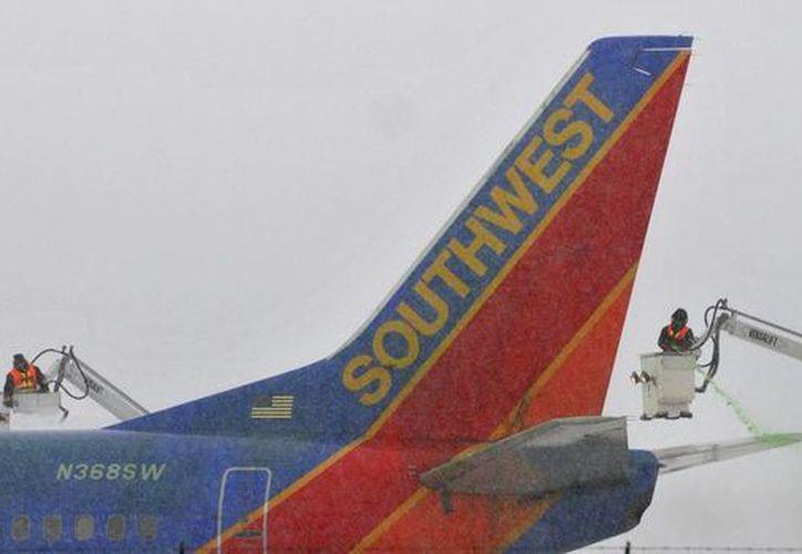 Las cuadrillas trabajan en el deshielo de un avión de Southwest en el aeropuerto internacional de Albany, en Colonie, NY. (Agencias)