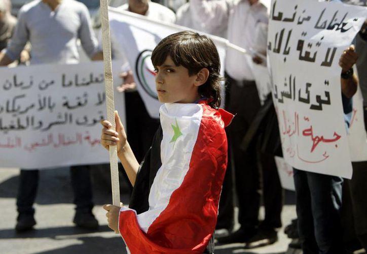 Una joven palestina envuelta en una bandera siria protesta contra la posible intervención de EU en Siria. (Agencias)