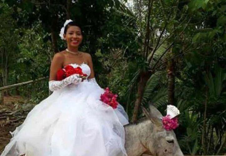 Al terminar la fila del cortejo, aparece la novia montada sobre un burro desde el que saluda y sonríe a los invitados del festejo. (Foto: Facebook)