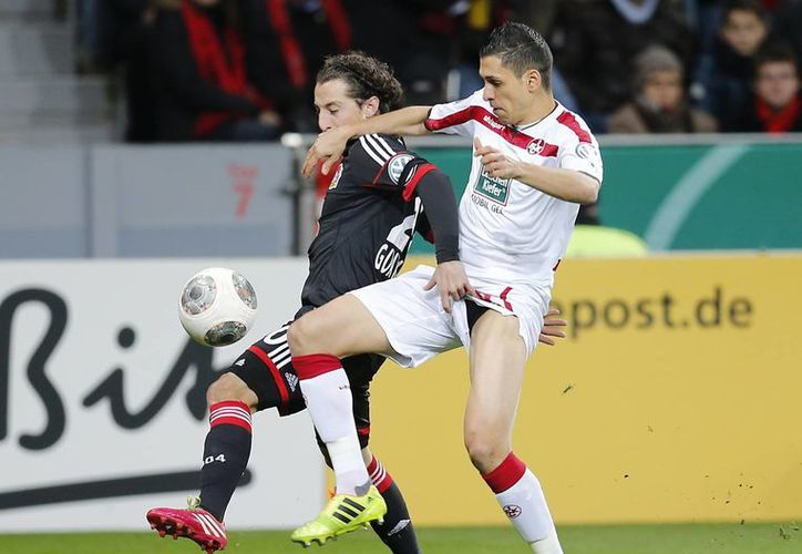 Guardado, nuevo jugador del Leverkusen, en disputa del balón con Karim Matmour, del Kaiserslautern, que eliminó al equipo del mexicano. (Agencias)
